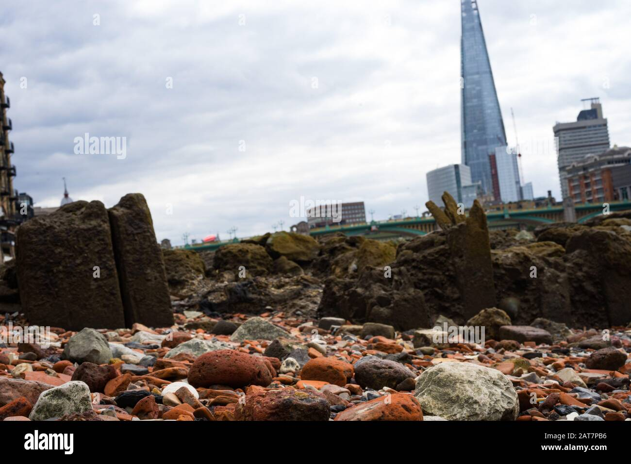 Pebbles on the foreshore of the River Thames looking towards  the shard building. A popular place for mudlarking and archaeological finds. Stock Photo