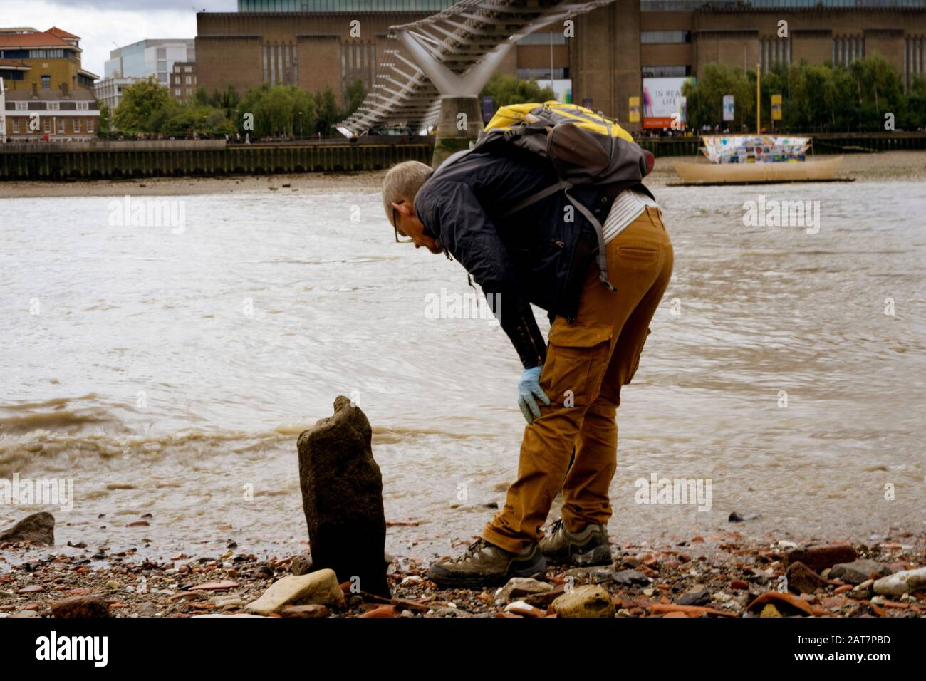 Mudlarking on the Thames foreshore looking towards the Tate Modern. With ancient posts exposed, its is a popular place for mudlarking and archaeological finds. Stock Photo