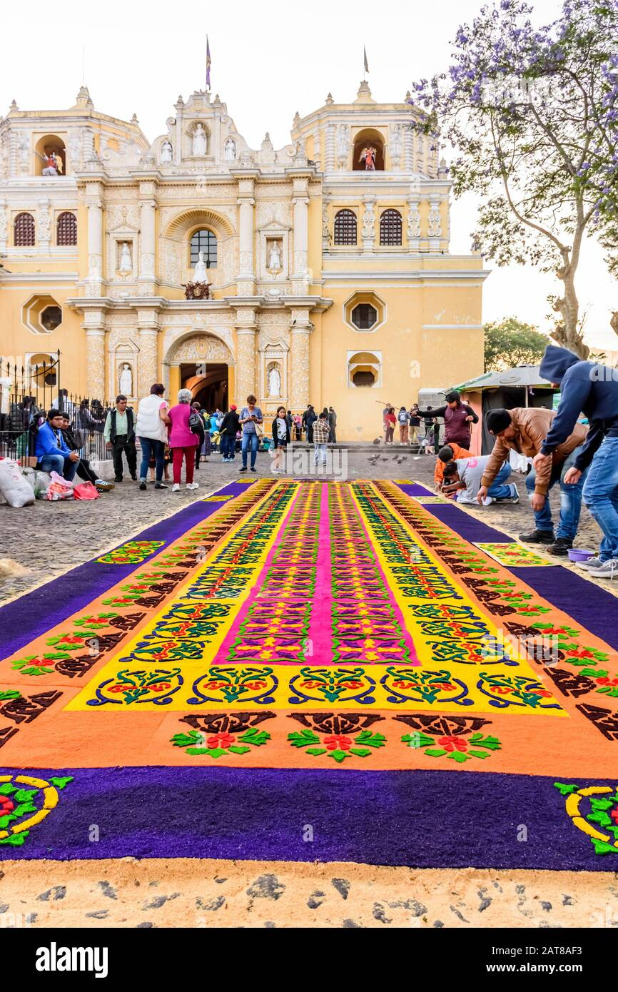 Antigua, Guatemala -  April 14, 2019: Making dyed sawdust Palm Sunday procession carpet by La Merced church in UNESCO World Heritage Site. Stock Photo