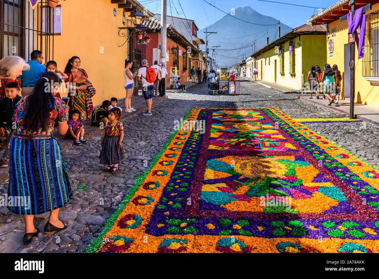 Antigua, Guatemala -  April 14, 2019: Maya family & Palm Sunday procession carpet with Agua volcano behind in UNESCO World Heritage Site. Stock Photo