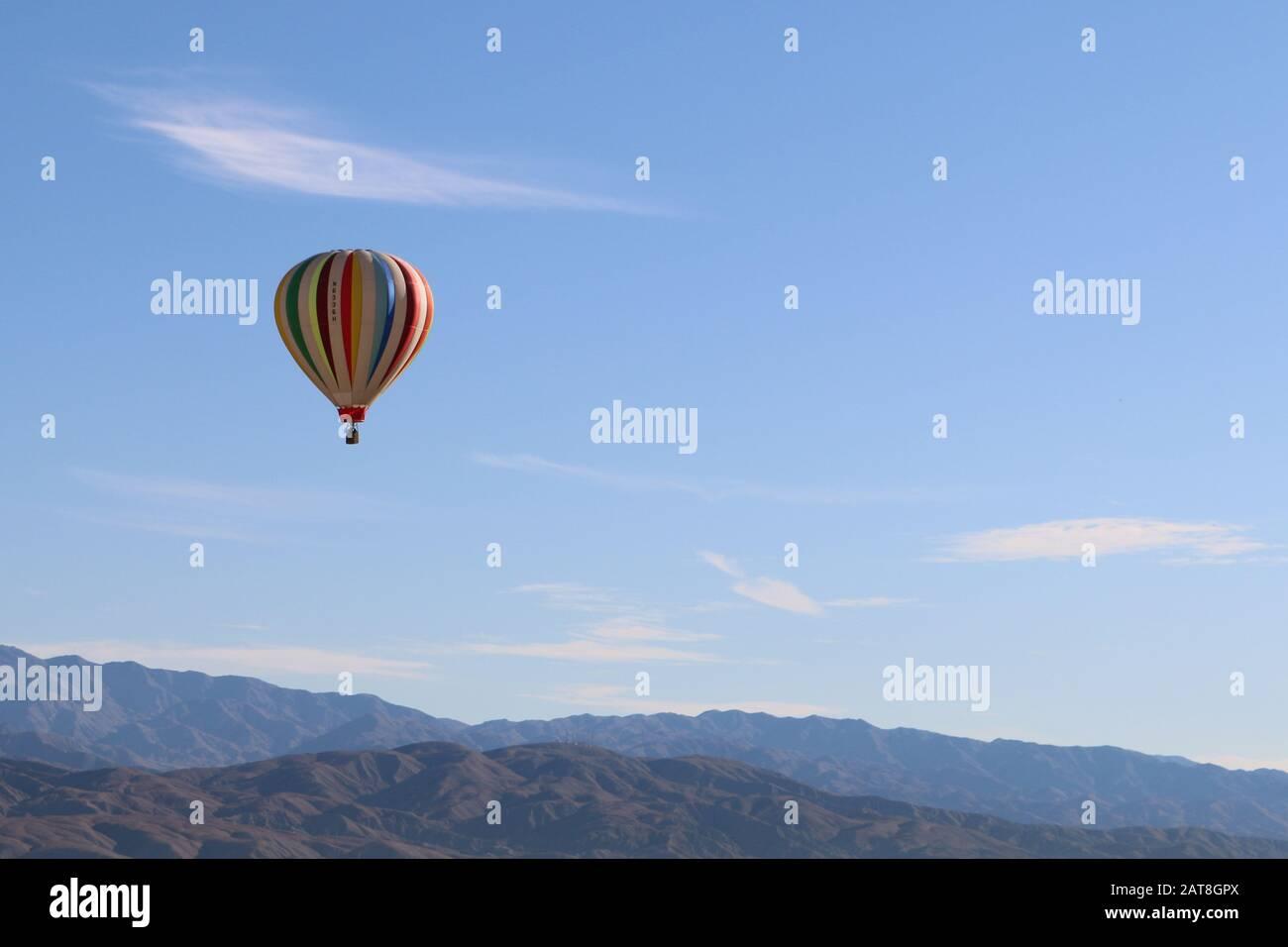 a hot air balloon sky over mountains and desert Stock Photo