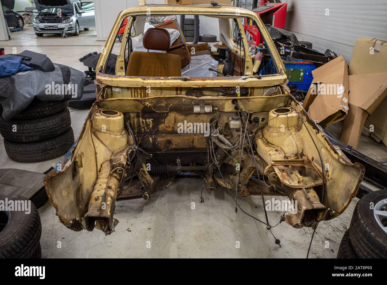 in a garage there is a disassembled old car wreck to be restored Stock Photo