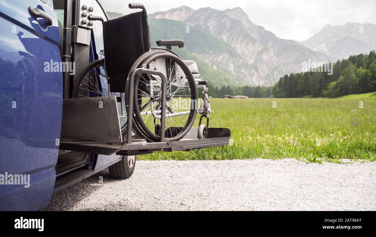 Photo of black electric lift specialized vehicle for people with disabilities. Empty wheelchair on a ramp with nature and mountains in the back Stock Photo