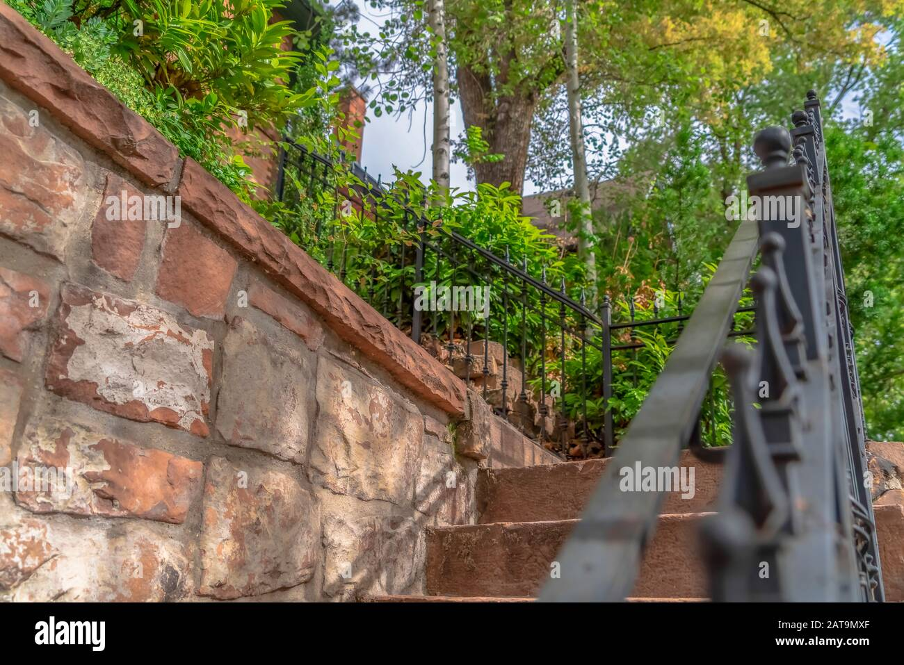 Close Up Of Outdoor Stairs With Black Metal Handrail Against A Stone Wall Stock Photo Alamy
