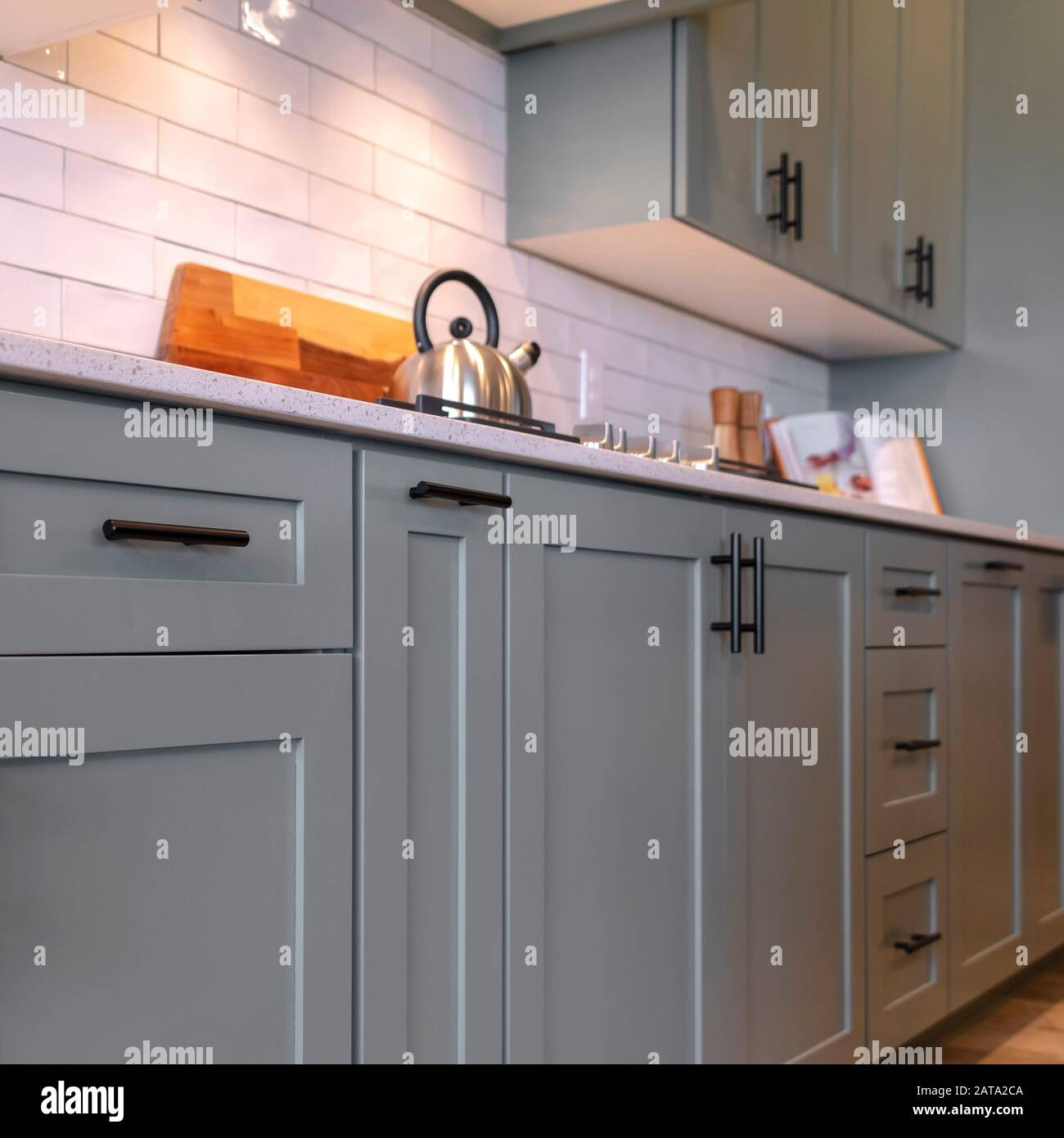 Photo Square Kitchen Cabinets With White Countertop Black Handles And Tile Backsplash Stock Photo Alamy