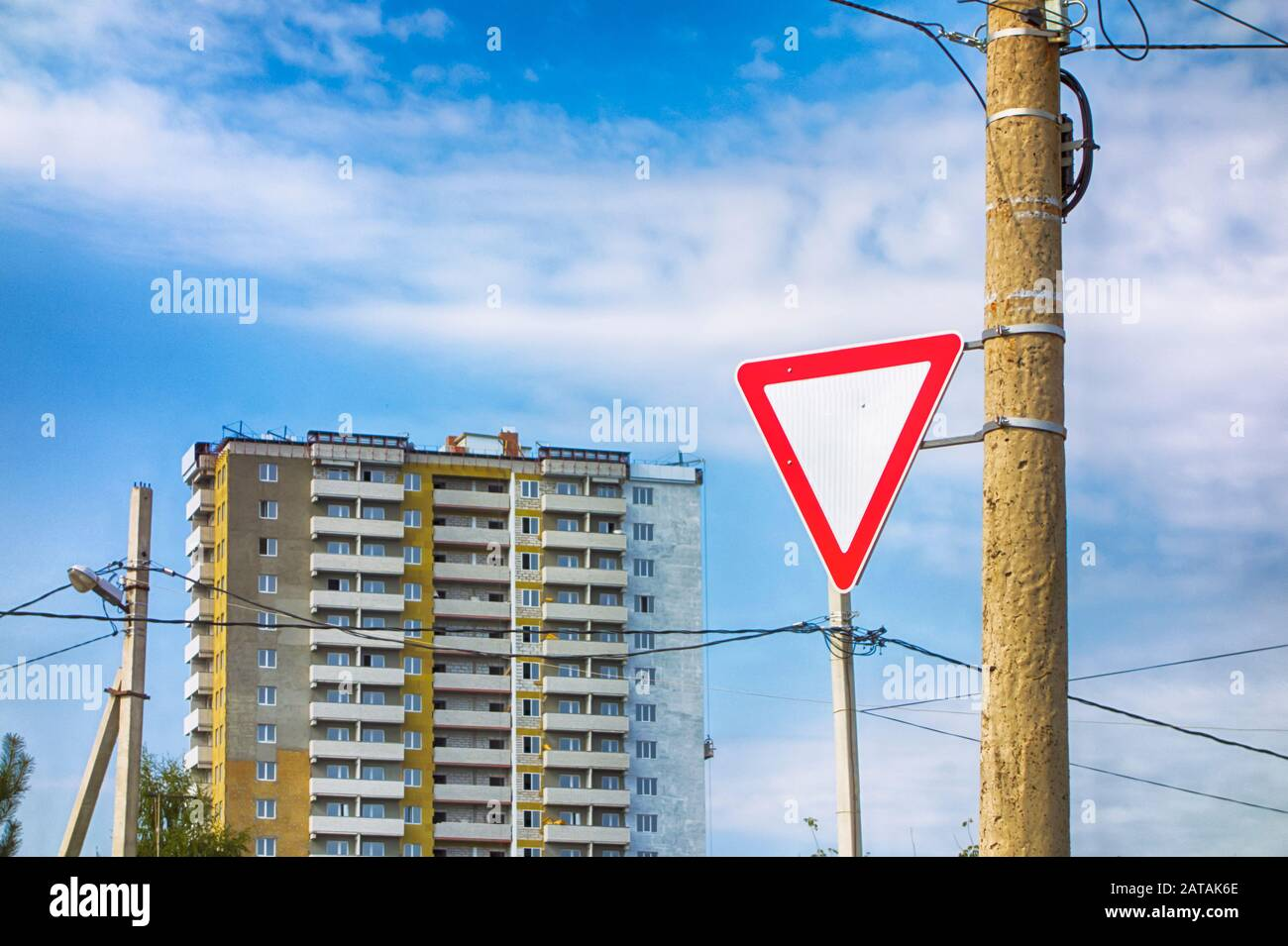 Give way road sign on pillar against multi-storey building and cloudy sky. Stock Photo