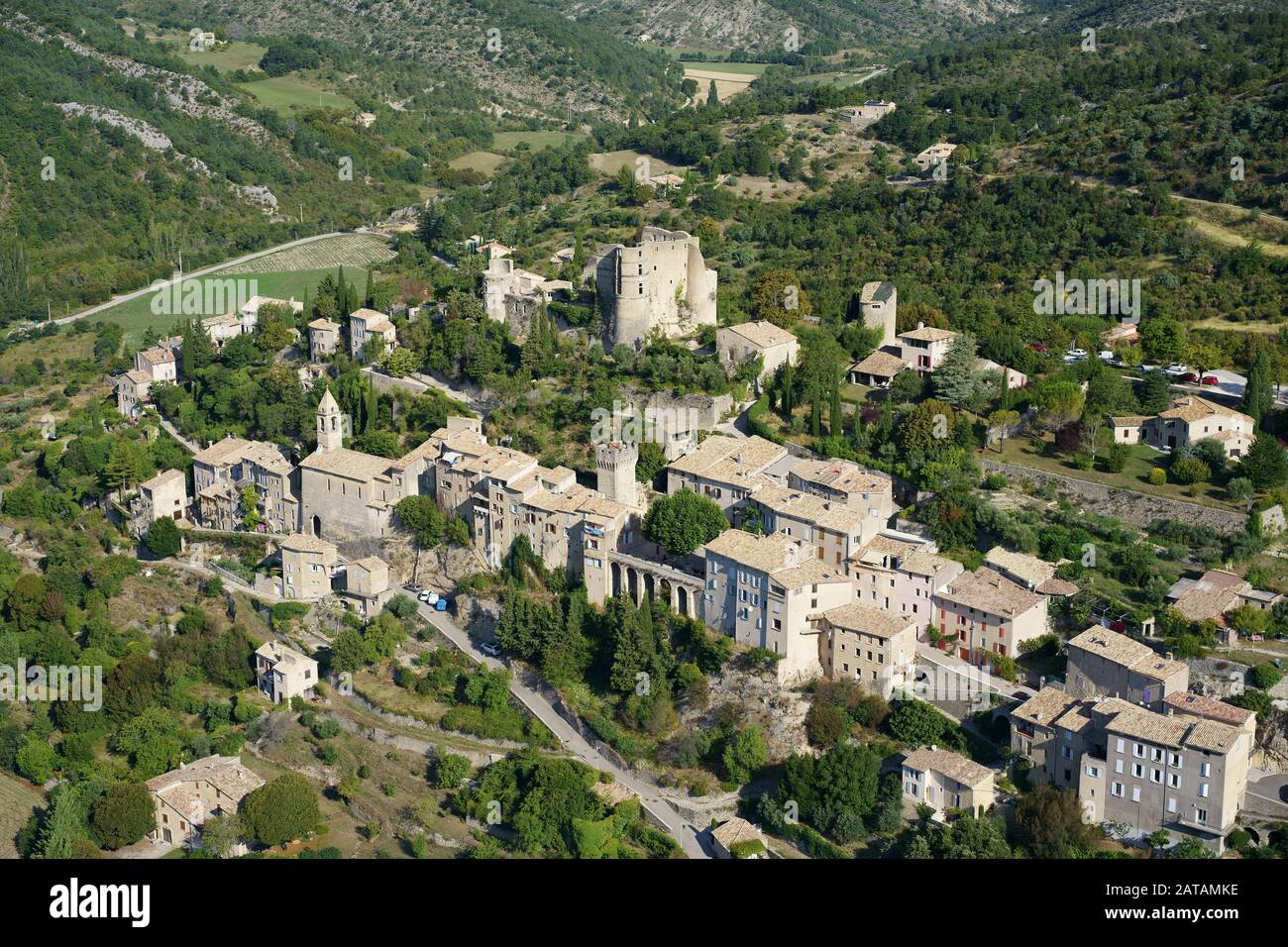 PROVENCAL VILLAGE BUILT ON A HILL, CROWNED WITH A MEDIEVAL CASTLE IN RUINS (aerial view). Montbrun-les-Bains, Drome, France. Stock Photo
