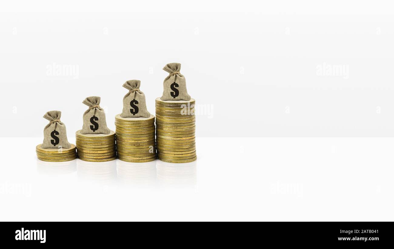 Money savings and investment banner concept. Money bag on rise stacked of coins on white background and space. Demonstrating long-term lasting wealth Stock Photo