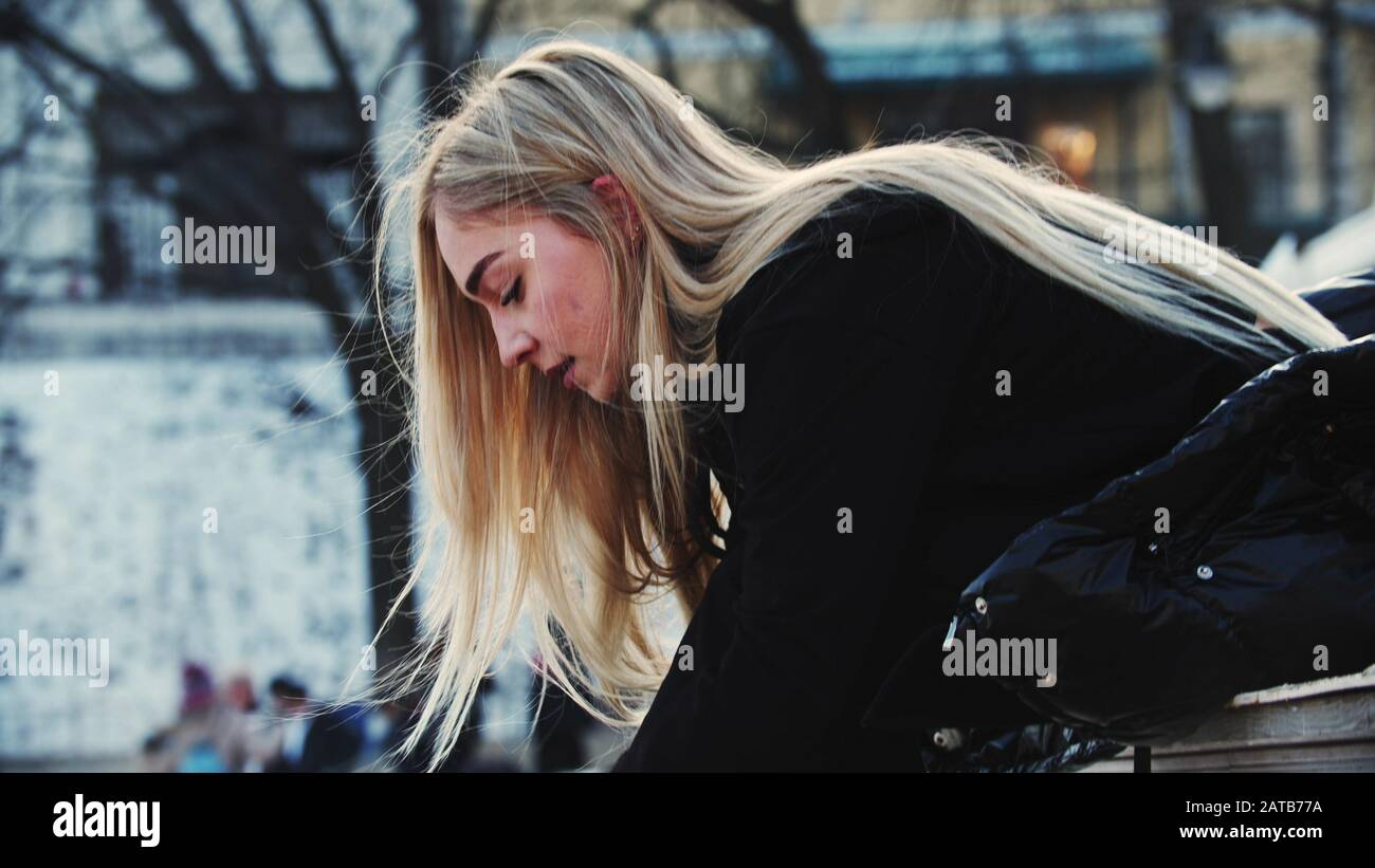 A young attractive woman with blond hair tie up her figure skates Stock Photo
