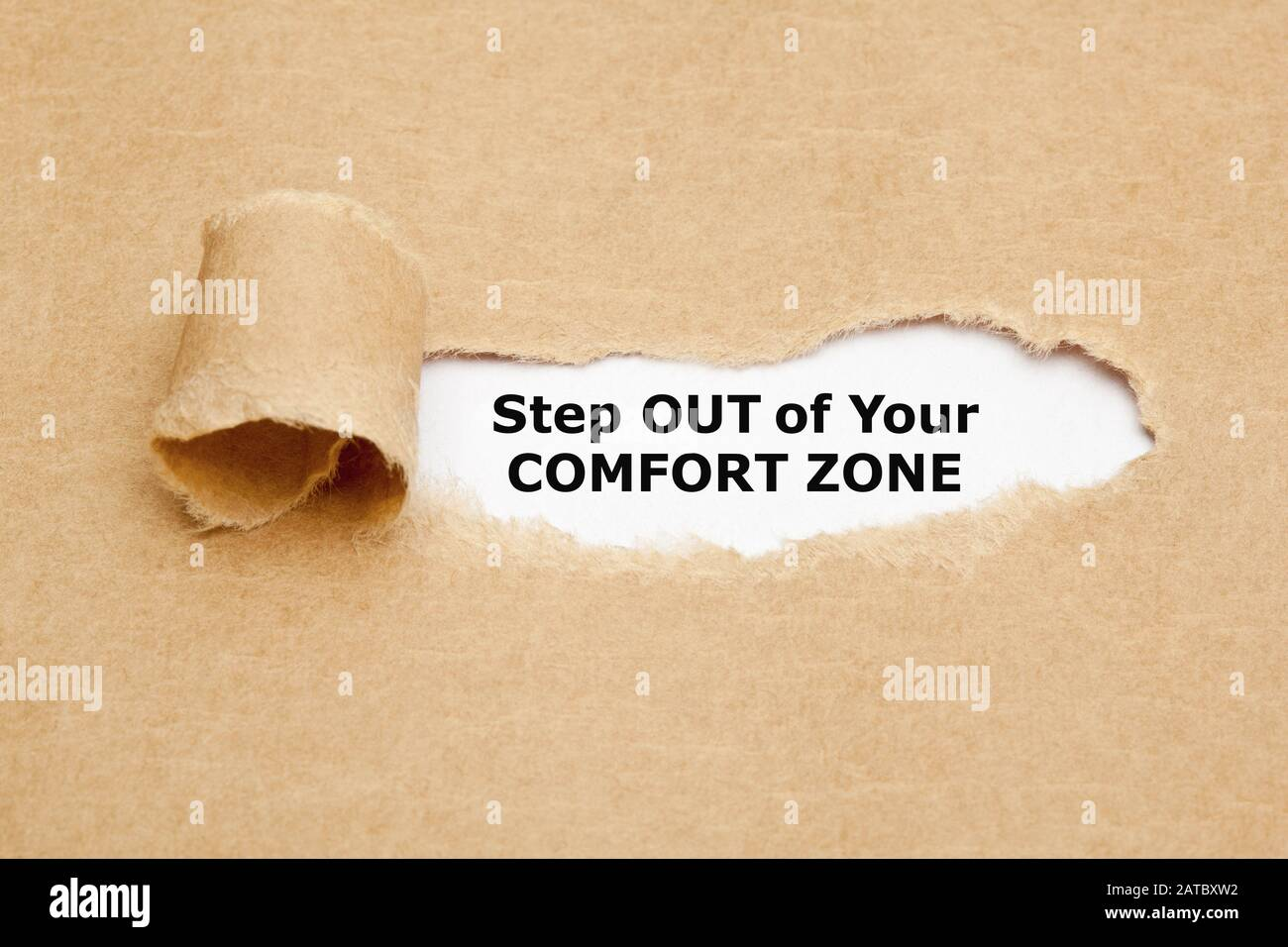 Motivational quote Step out of your comfort zone. appearing behind ripped brown paper. Stock Photo