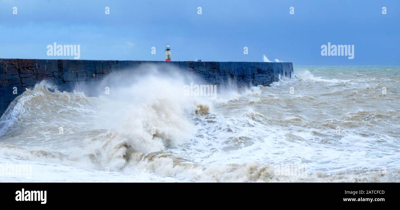 A harbor wall with a rough stormy sea crashing against the wall causing the sea to be blurred and in motion, behind is a red and white lighthouse, wav Stock Photo