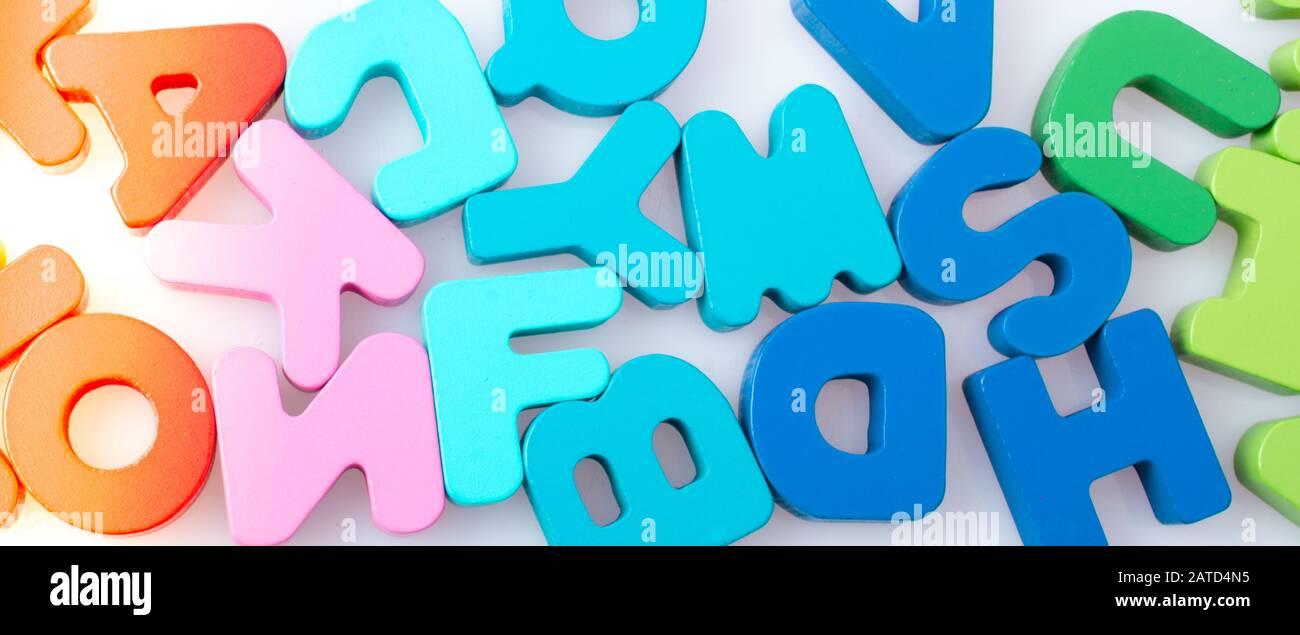 Colorful alphabet letter blocks scattered randomly on white background Stock Photo