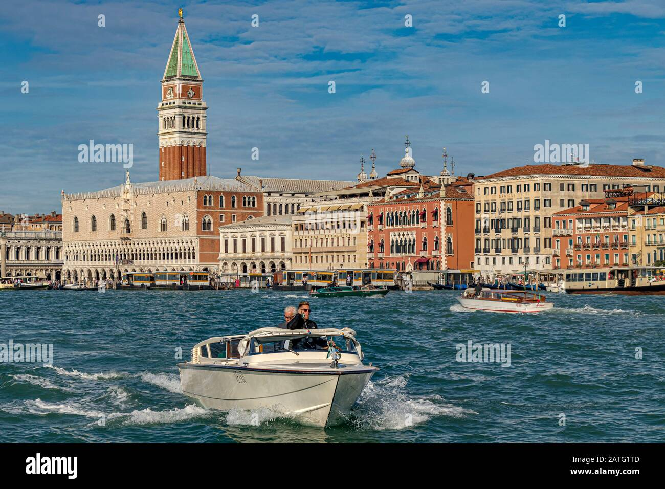 A Water taxi speeds along The waterfront near Piazza San Marco with St Marks Tower and The Doges Palace in the distance ,Venice,Italy Stock Photo