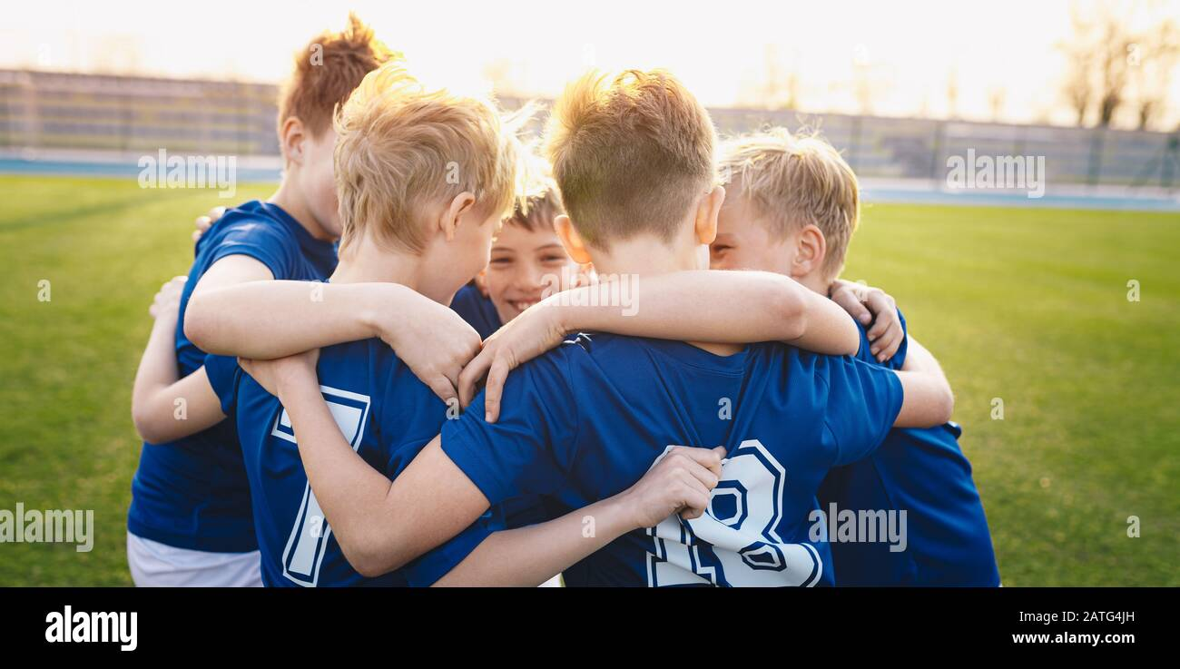 Happy kids in elementary school sports team celebrating soccer succes in tournament final game. Children soccer team team gathering together in a circ Stock Photo