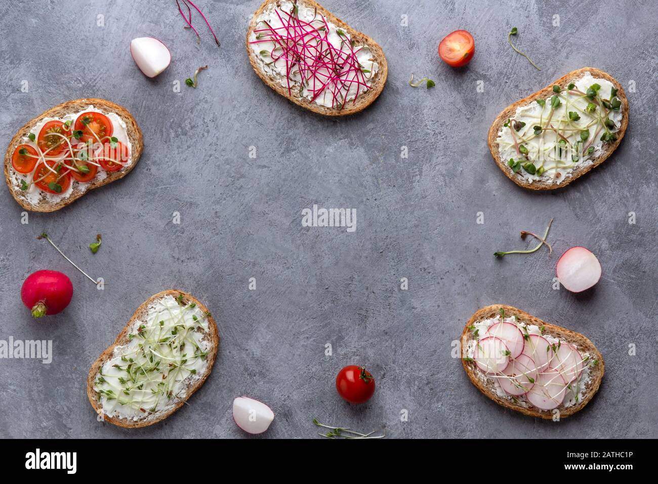 A frame of sandwiches with vegetables and microgreens on a gray concrete background. Copy space in the center Stock Photo