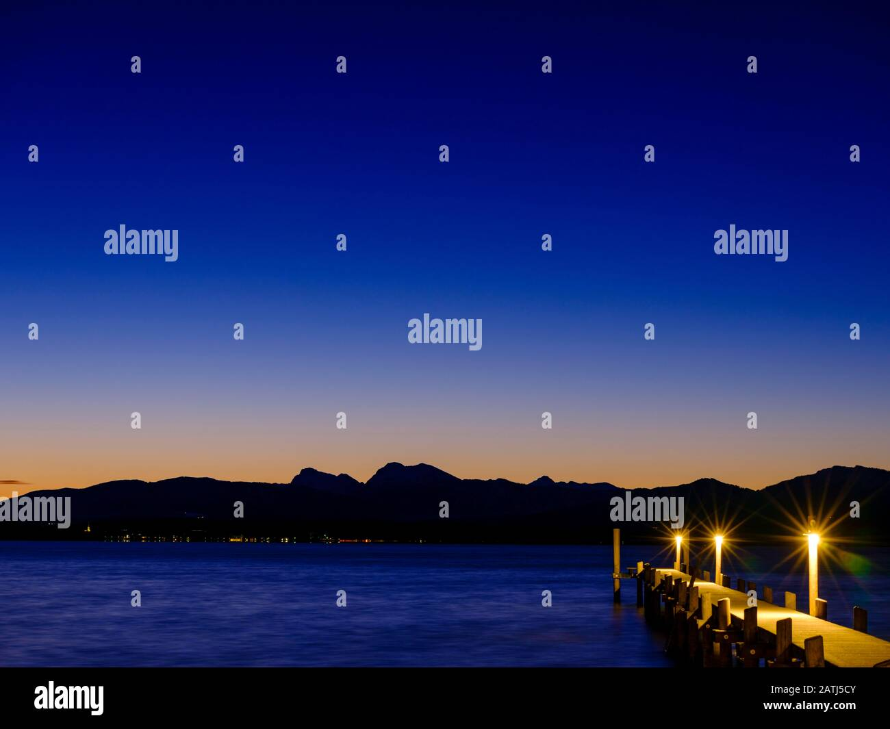 Footbridge at Chiemsee at dawn, behind the Chiemgau Alps, Chiemgau, Upper Bavaria, Bavaria, Germany Stock Photo
