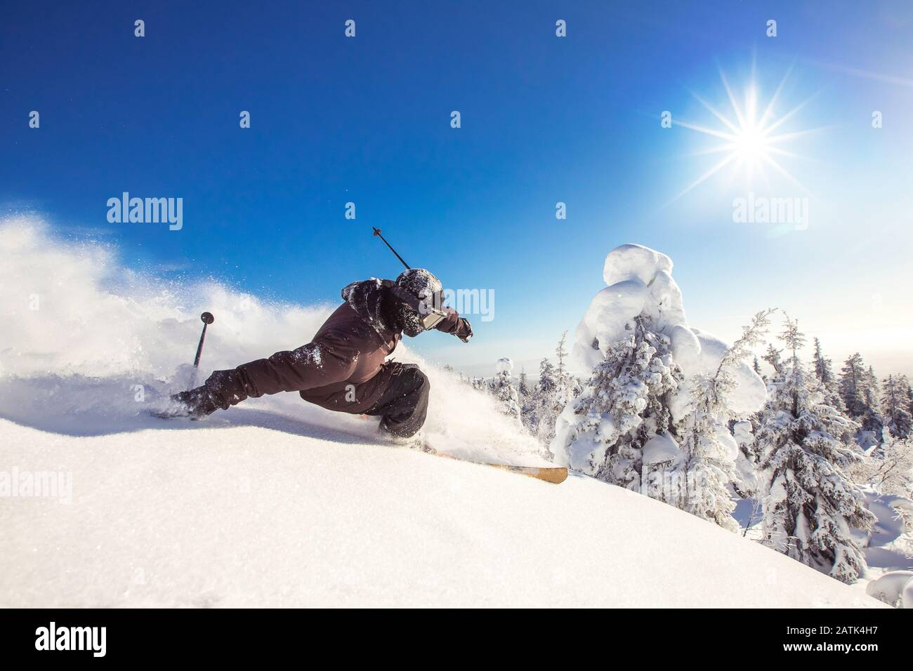 Skier skiing downhill during sunny day fresh snow freeride. Extreme High speed, frosty dust scatters Stock Photo
