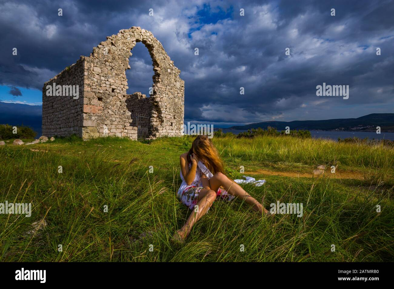 Country-girl sitting in grass in field countyside countrygirl looking down hiding head face identity unknown flying golden hair because of wind windy Stock Photo