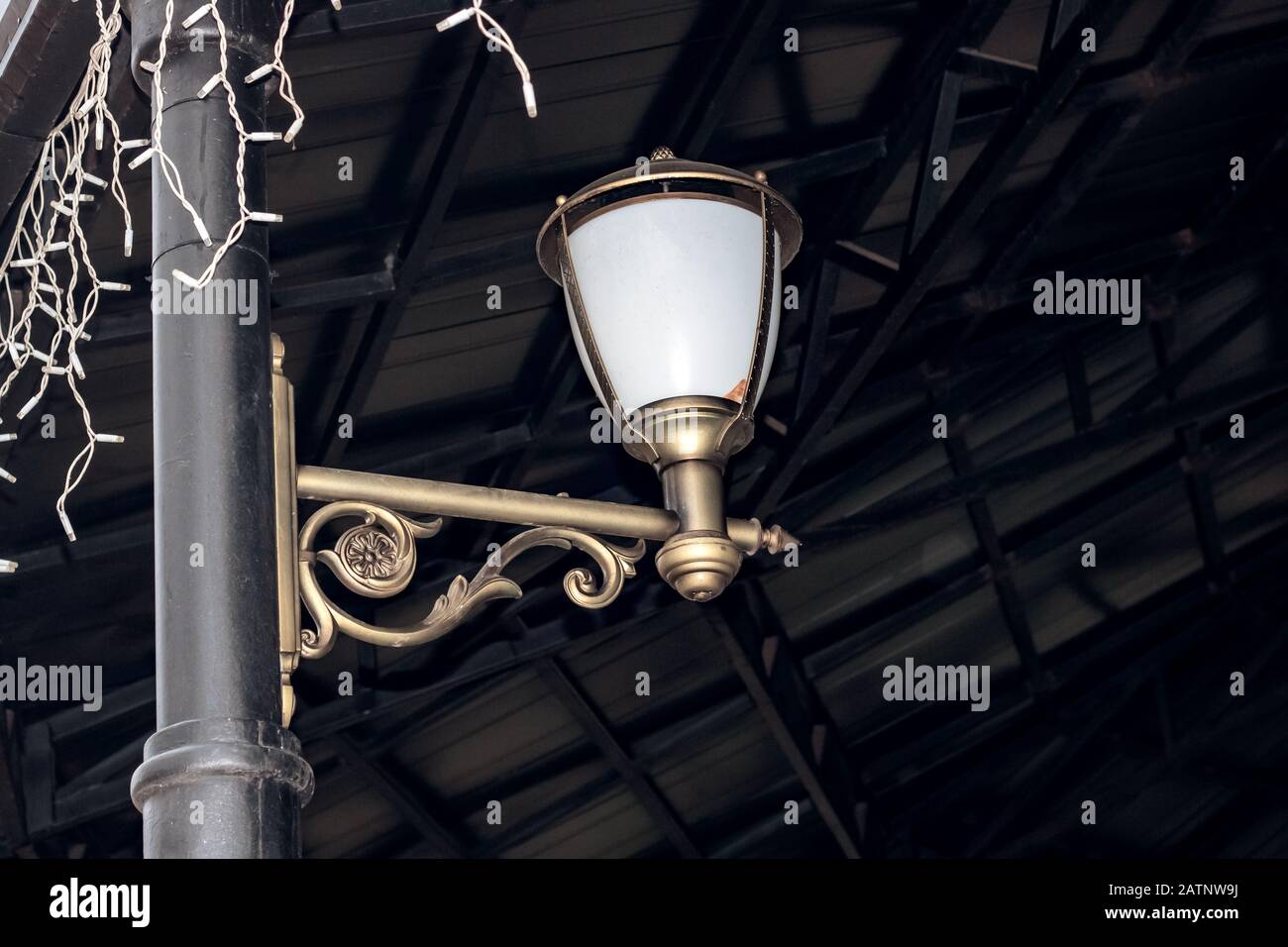 White lantern in retro style on a pillar of a forged arbor Stock Photo