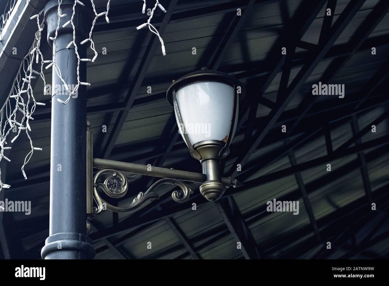 White lantern in retro style on a pillar of a forged arbor Stock Photo