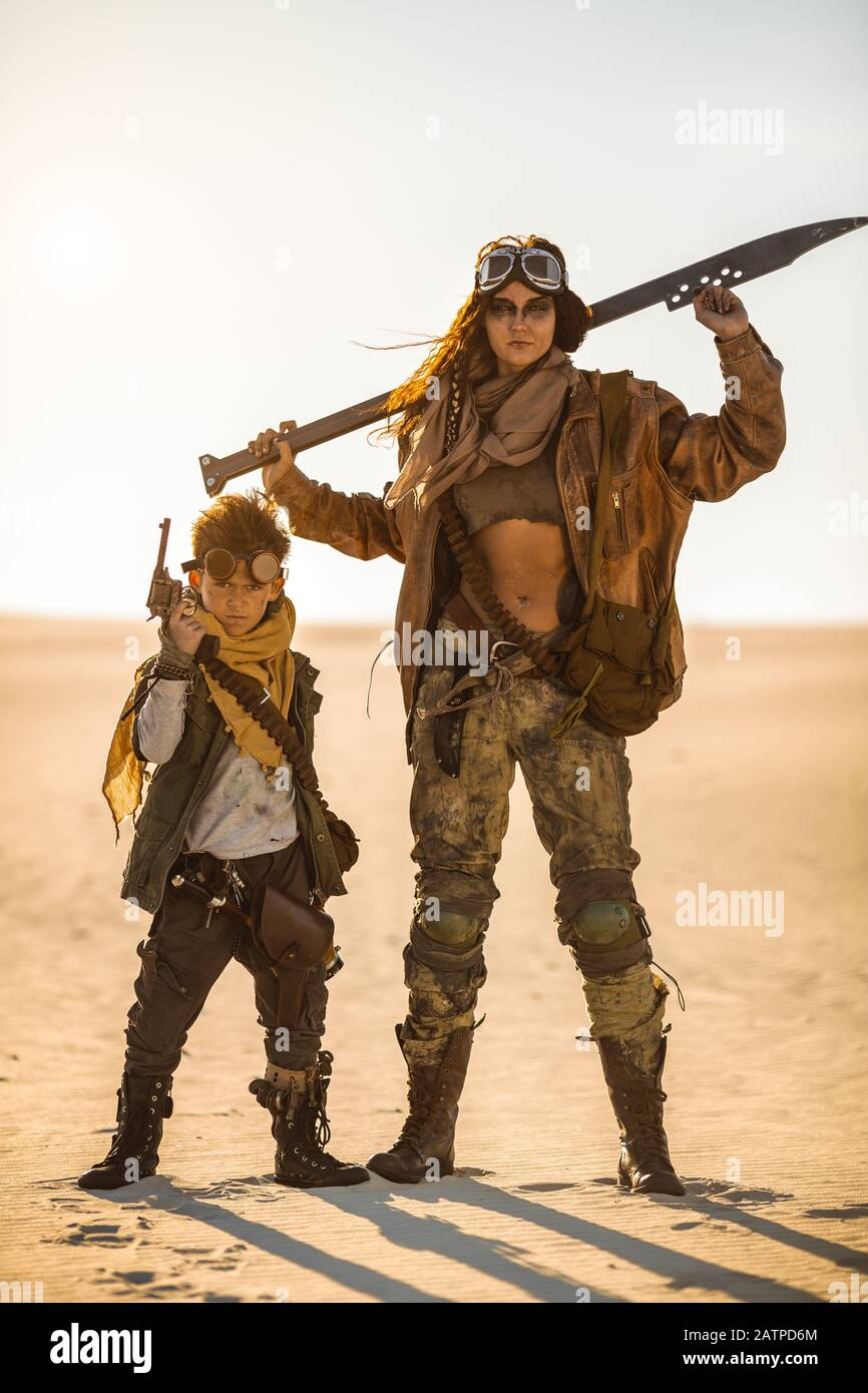 Post-apocalyptic woman and boy with weapons outdoors. Desert and dead wasteland on the background. Aggressive girl warrior in shabby clothes holding the sword and young boy with a gun standing in a confident pose looking at the camera. Nuclear post-apocalypse time. Life after doomsday concept.