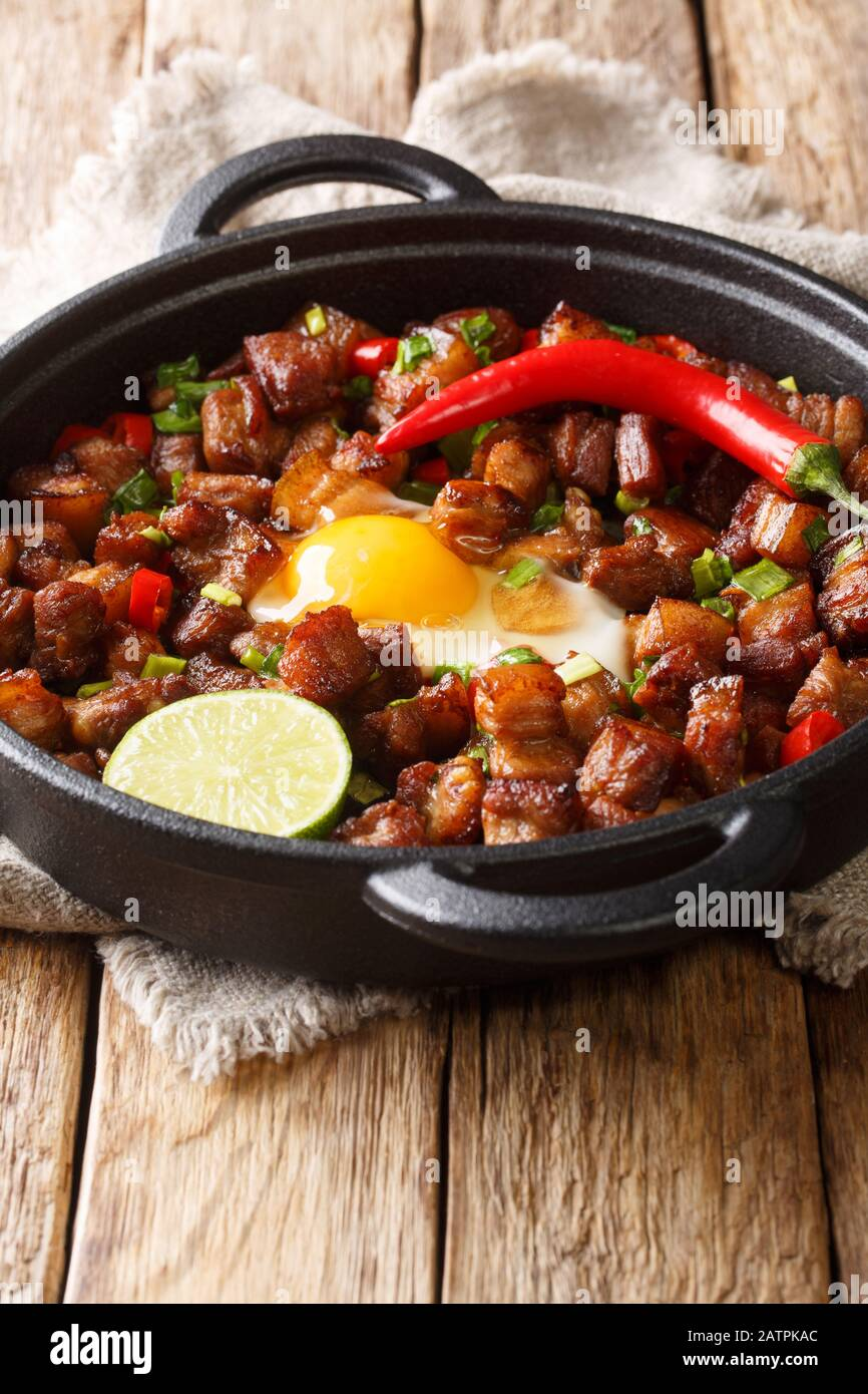 Sisig Is A Filipino Dish Made From Parts Of Pig Head And Chicken Liver Usually Seasoned With Onions And Chili Peppers Close Up In A Pan On The Table Stock Photo Alamy