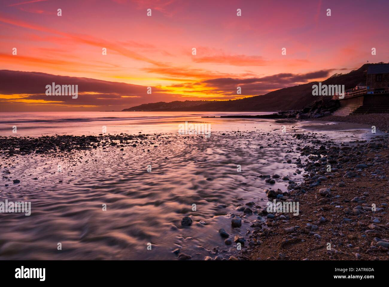 Charmouth, Dorset, UK.  4th February 2020. UK Weather.  A spectacular fiery sunset at the beach at Charmouth in Dorset looking west along the coast towards Lyme Regis.  Picture Credit: Graham Hunt/Alamy Live News Stock Photo