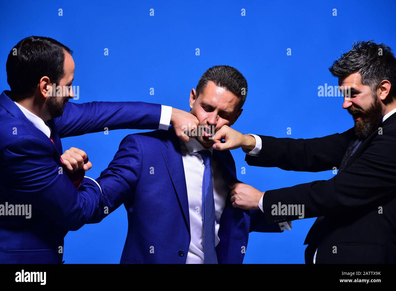 Business conflict and argument concept. Coworkers decide upon best working position. Company leaders fight for business leadership. Businessmen with rage faces in formal wear on blue background Stock Photo