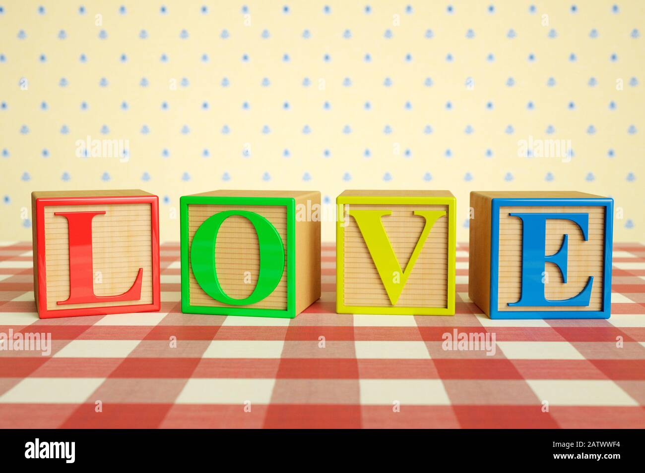 Childrens wooden ABC blocks spelling LOVE on a checked tablecloth Stock Photo