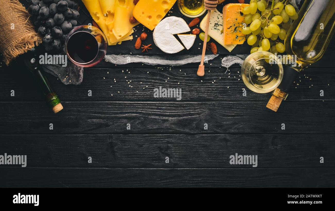 A large assortment of cheeses, brie cheese, gorgonzola, blue cheese, grapes, honey, nuts, red and white wine, on a wooden table. Top view. Free space Stock Photo