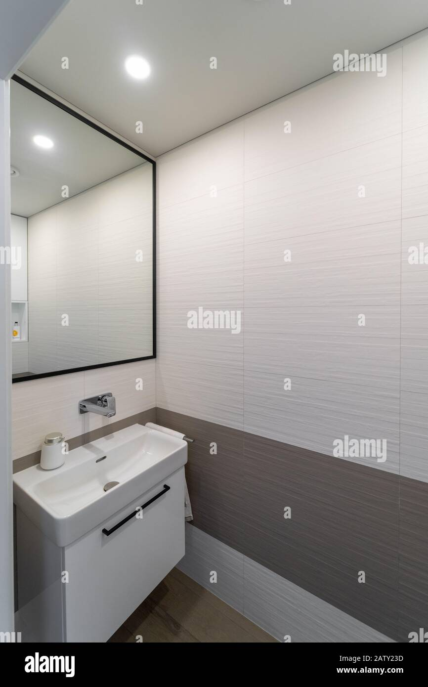 Picture of: Modern New Light Colored Toilet Interior With Beige And Brown Wall And Floor Tiles White Sink On The Cupboard Next To It A Towel Hanging Above I Stock Photo Alamy