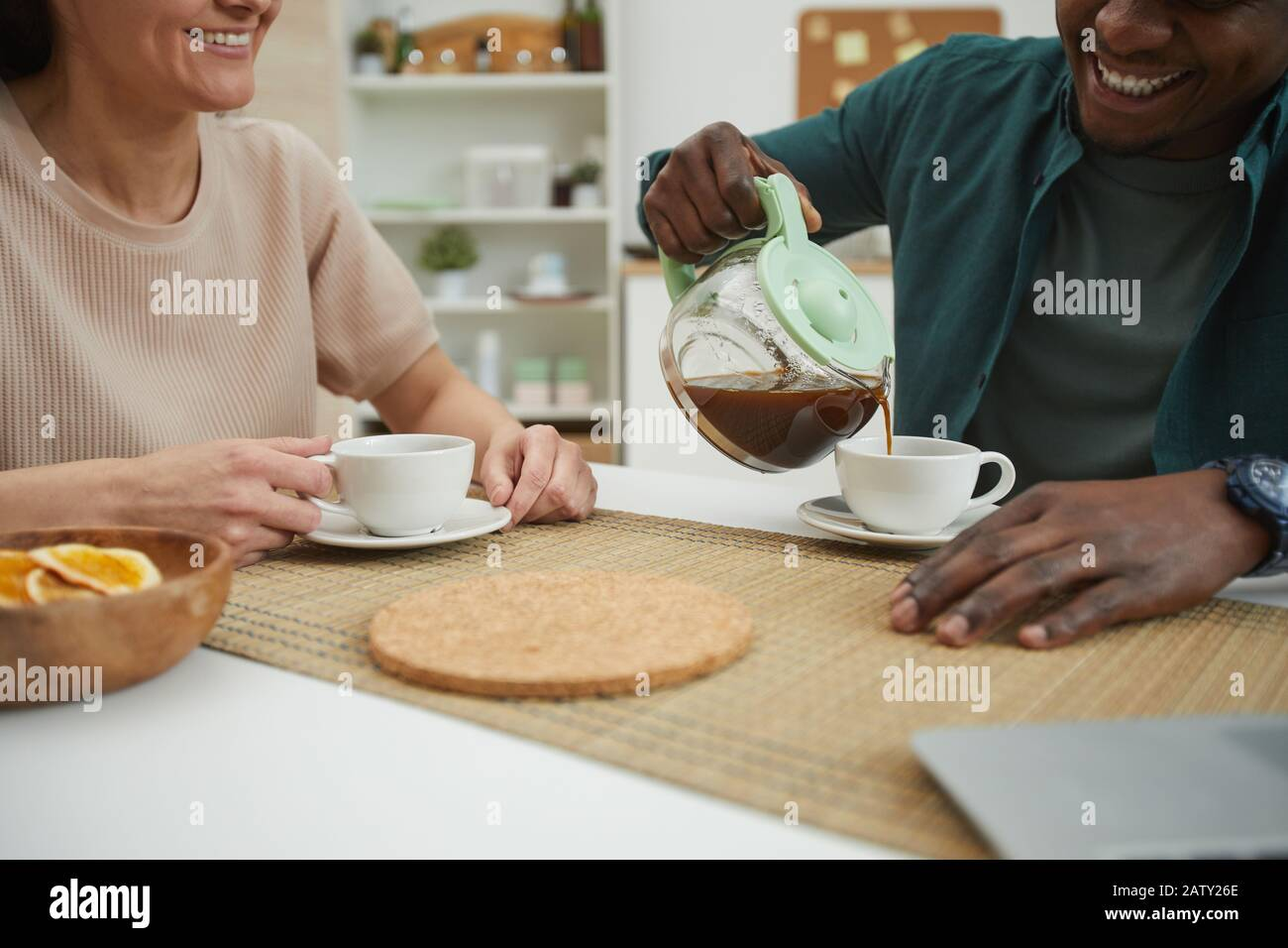 Close-up of young multiethnic couple enjoying each other and drinking coffee at the table in the domestic kitchen Stock Photo