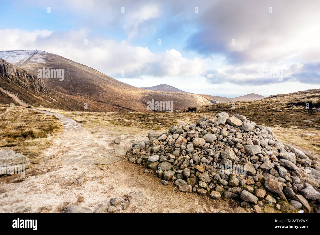 Footpath leading to snow capped peak of Slieve Donard mountain. Pile of stones in Mourn Mountains, most dramatic and highest range in Northern Ireland Stock Photo
