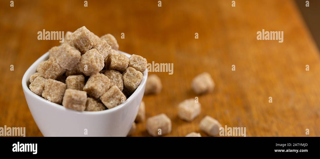 cup full of pieces of brown sugar on a wooden table with a blurred background Stock Photo