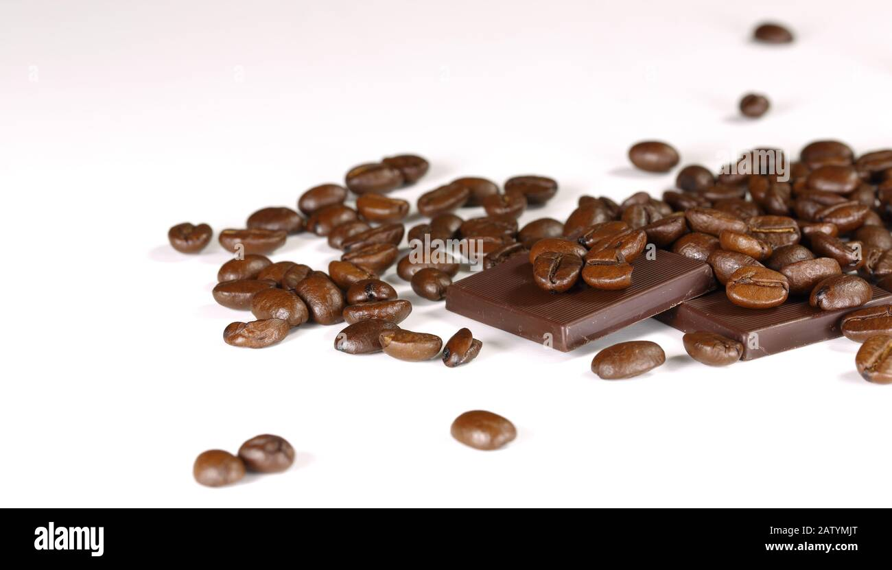 coffee beans on a white background with pieces of black chocolate Stock Photo