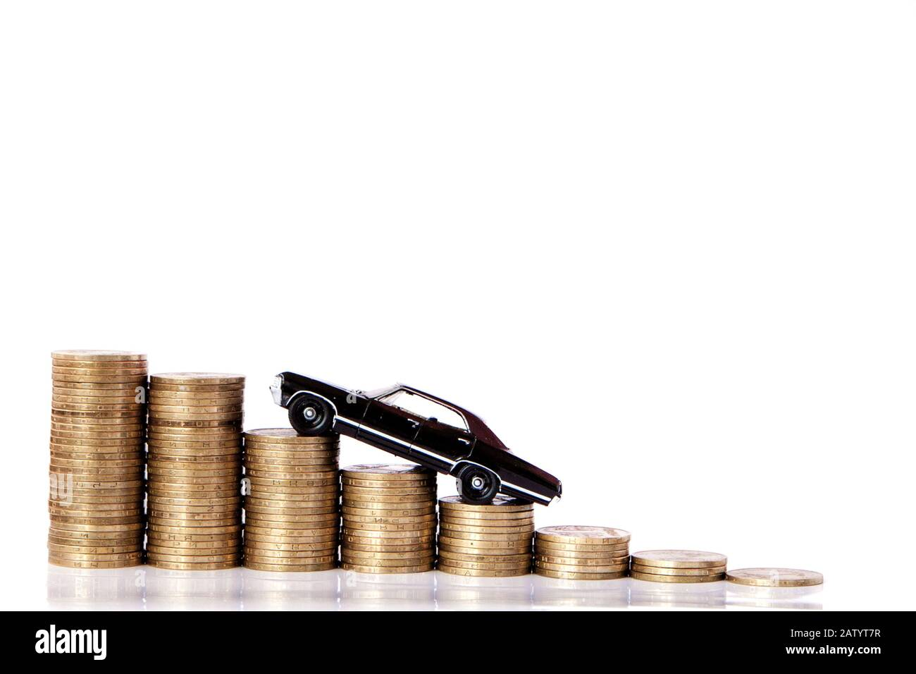 A black model of a car with coins in the form of a histogram on a white background. Concept of lending, savings, insurance. Stock Photo