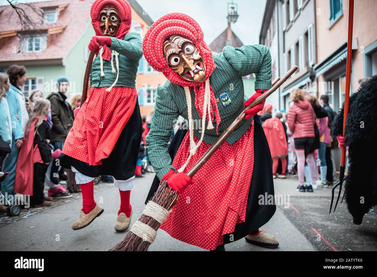 Kandel witch from Waldkirch, beautiful witch in blue and red slowly approaches and leans on the broom. During the carnival parade in Staufen, southern Stock Photo