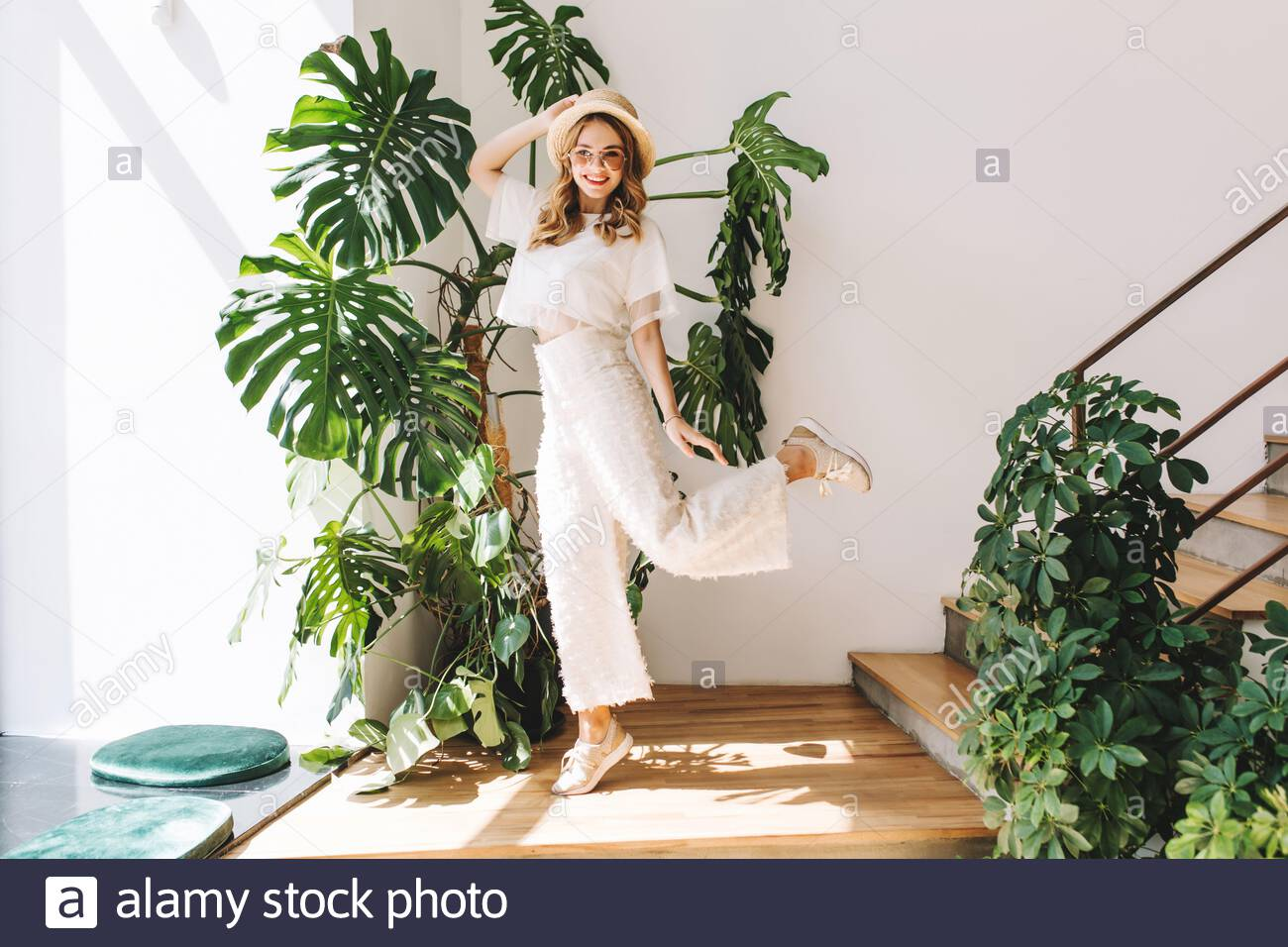 Ecstatic blonde girl in white pants funny dancing at home posing in front of big plant. Indoor portrait of jumping young woman in hat and glasses happy smiling next to stairs. Stock Photo