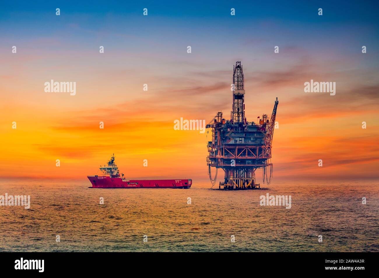 An ocean oil rig and supply ship in the South China Sea near Japan. Stock Photo
