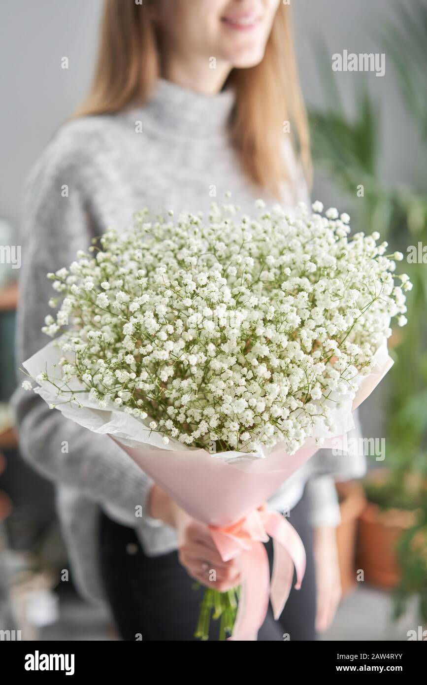 White gypsophila. Beautiful bouquet of mixed flowers in womans hands. the work of the florist at a flower shop. Fresh cut flower. Stock Photo