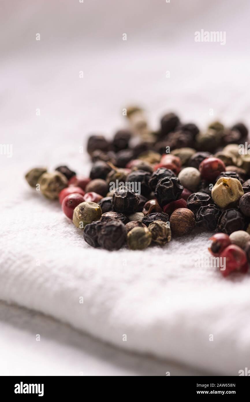 Pile of peppercorns on a white cloth napkin. Stock Photo