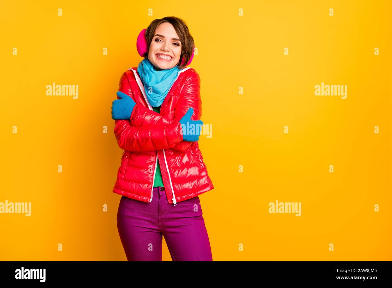 Photo of funny cheerful lady enjoy warm coat in frosty weather hug herself wear casual short red overcoat blue scarf gloves earmuffs pants isolated Stock Photo