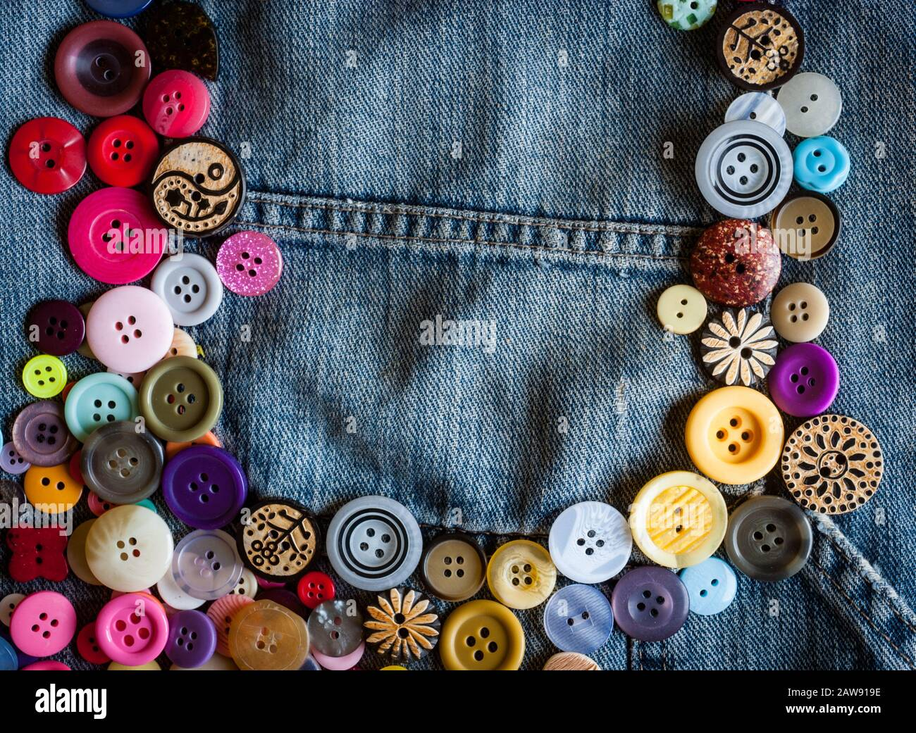 sewing buttons on denim jeans background Stock Photo