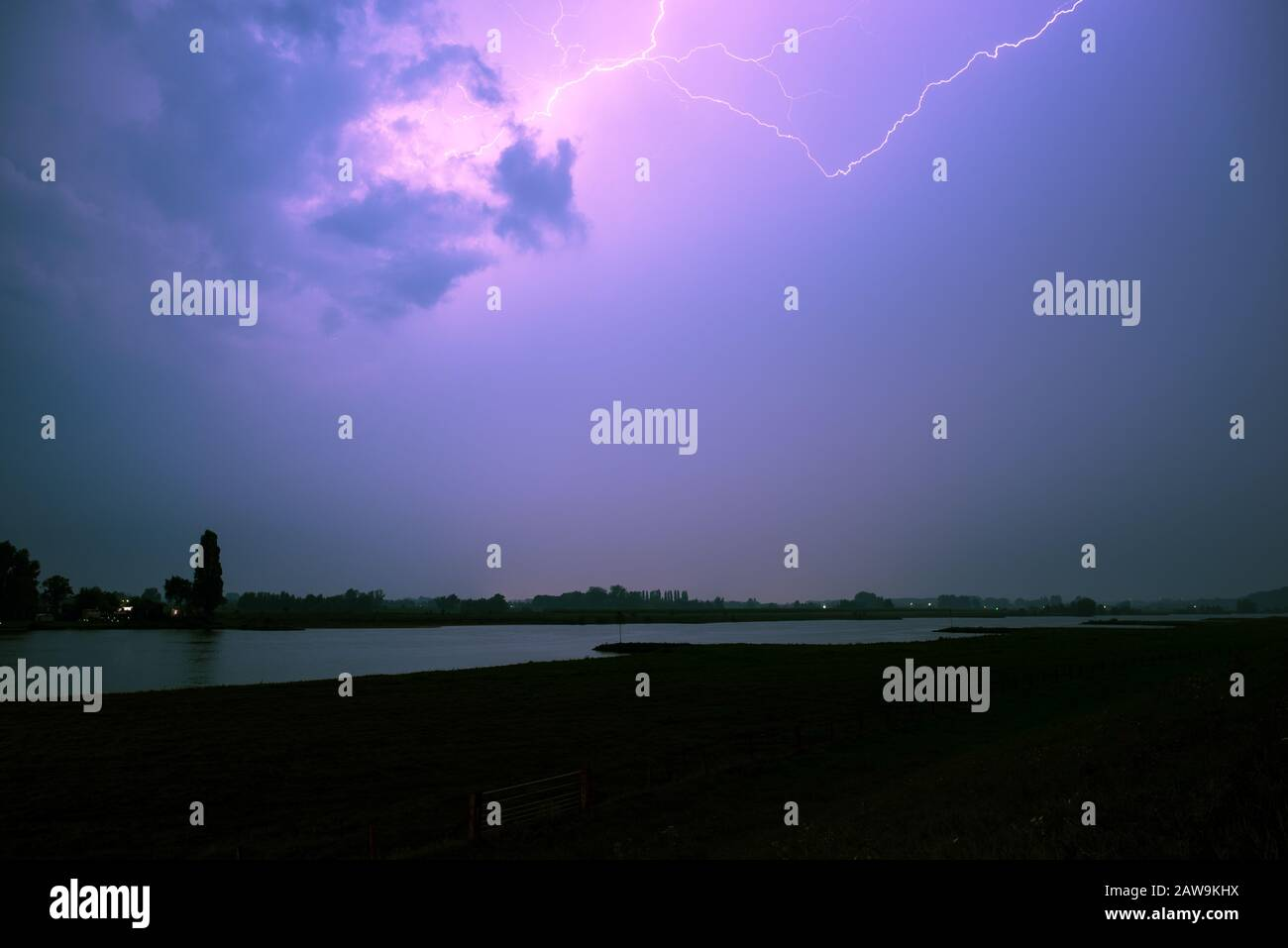 Stunning landscape image of lightning bolt in the sky over a river in central part of The Netherlands Stock Photo
