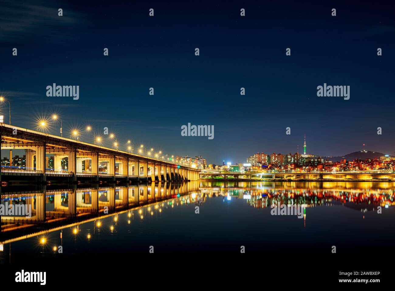 Bridges punctuate the skyline from the river's eye view along the Han River in Seoul, South Korea.  Namsan tower dominates the northern skyline. Stock Photo