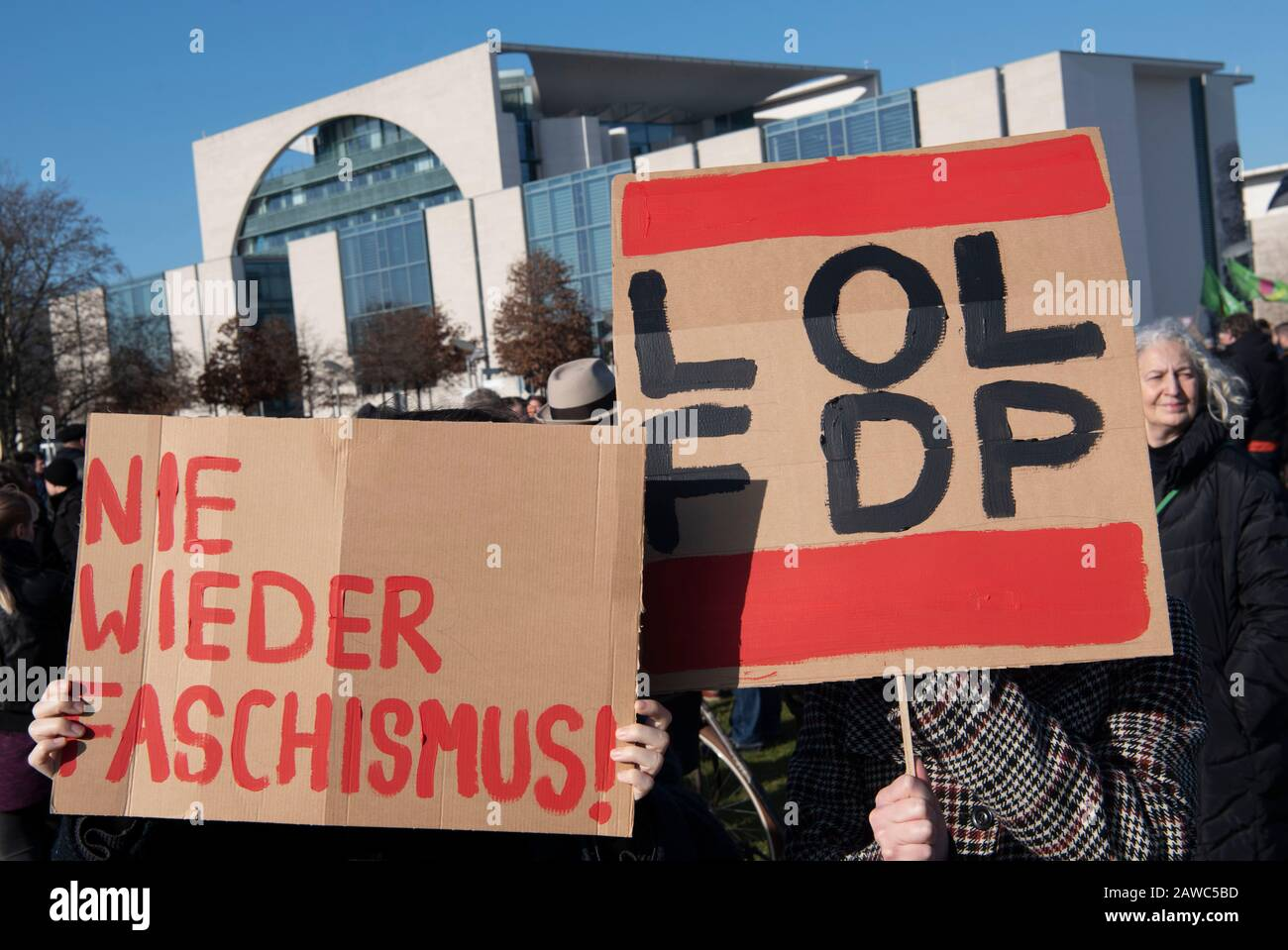 "Berlin, Germany. 08th Feb, 2020. Demonstrators are standing at the Reichstag during an action against right-wing and the events in Thuringia and protesting. Signs with the inscriptions ""NIE WIEDER FASCHISMUS!"" or ""LOL FDP"" are held up. Credit: Paul Zinken/dpa/Alamy Live News Stock Photo"