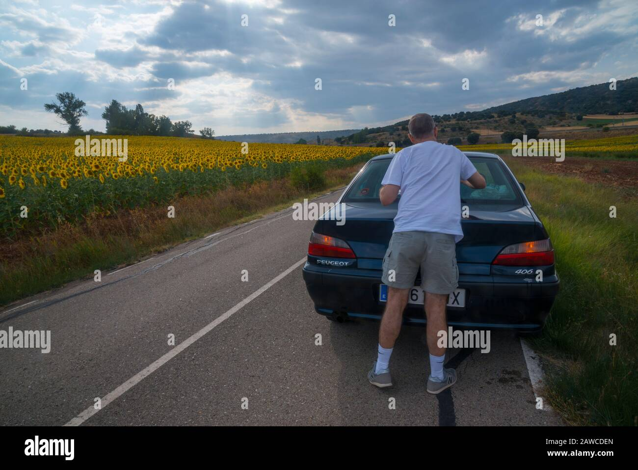 Man cleaning his car window in a side road. Stock Photo