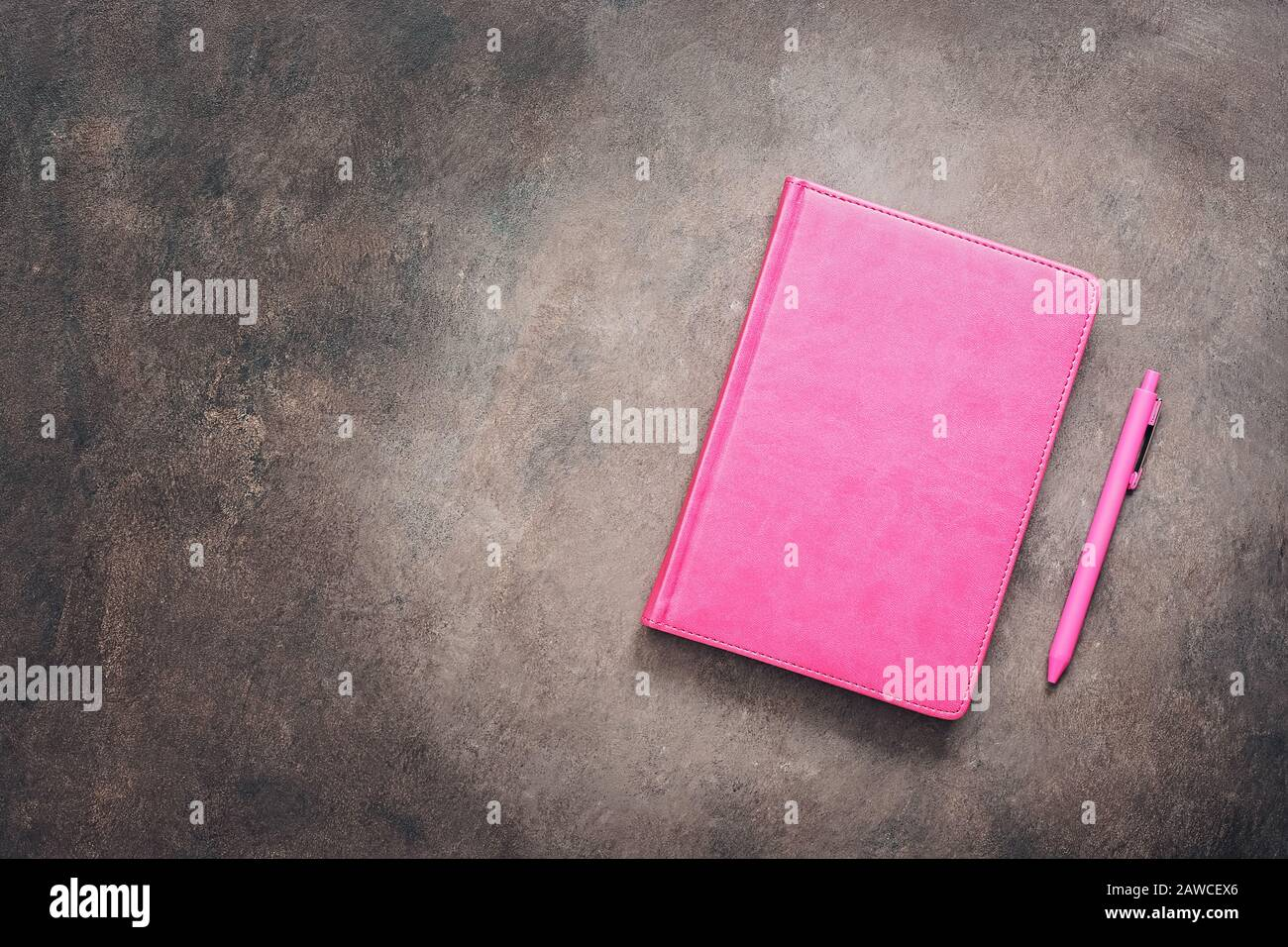 Pink notebook and pen on a dark vintage background, toned. Female workspace. Top view, flat lay, copy space Stock Photo