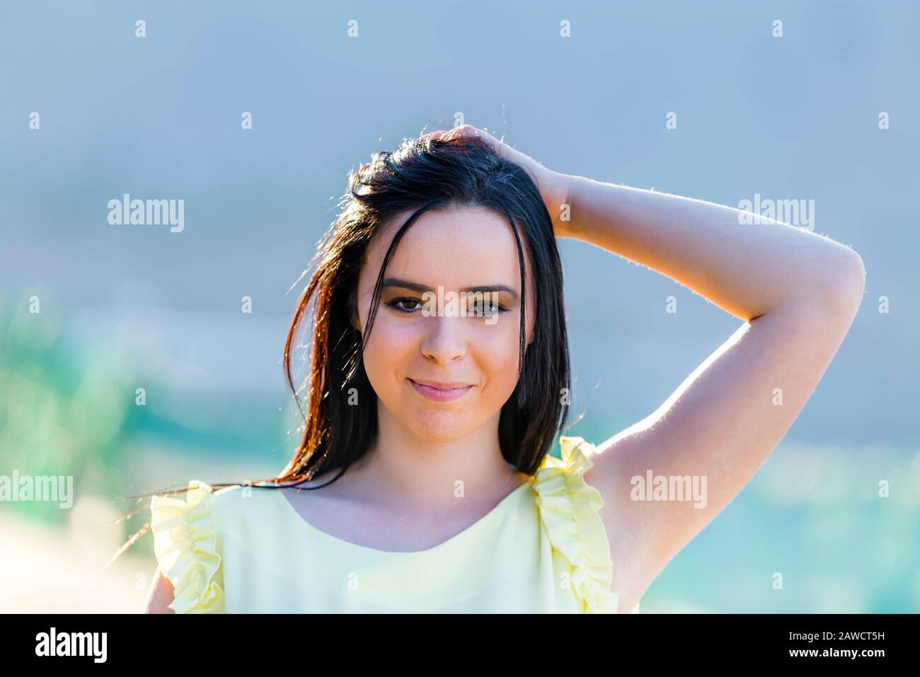 Teen girl portrait backlighted is going to smile looking at camera eyeshot eye eyes contact direct view head and shoulders hand arm behind raised Stock Photo