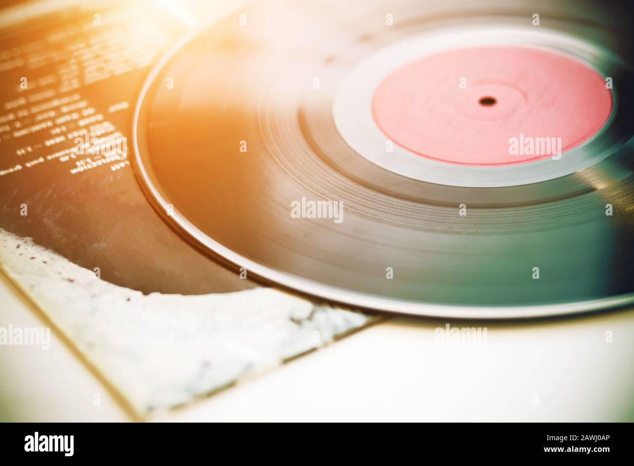 A vintage musical black vinyl record lies on the paper cover of a music album, illuminated by sunlight. Stock Photo